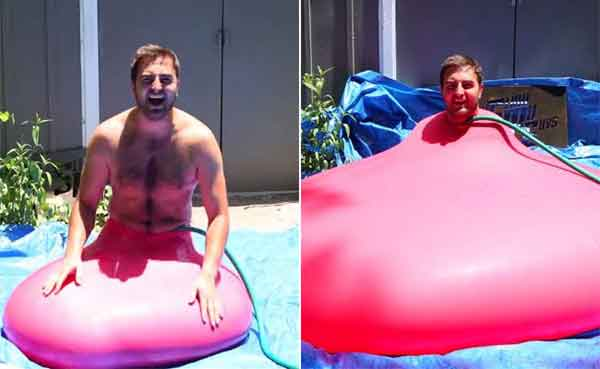 Giant water balloon bursts in slow motion with man inside
